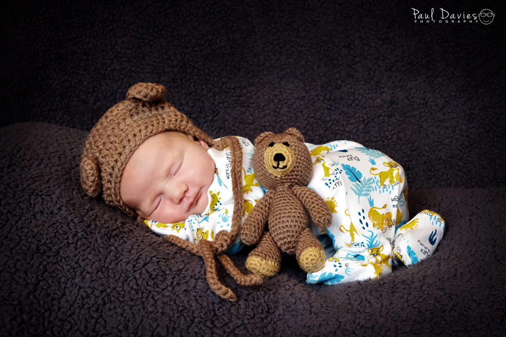 Baby in hat with teddy bear sleeping.