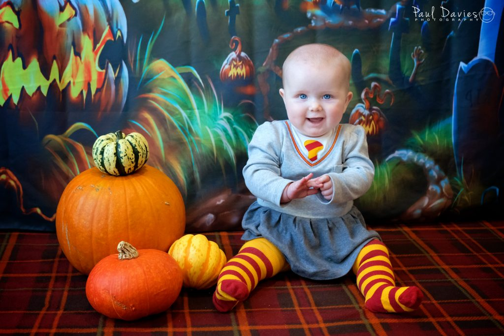 Baby dressed in Harry Potter outfit sitting with pumpkins at Halloween