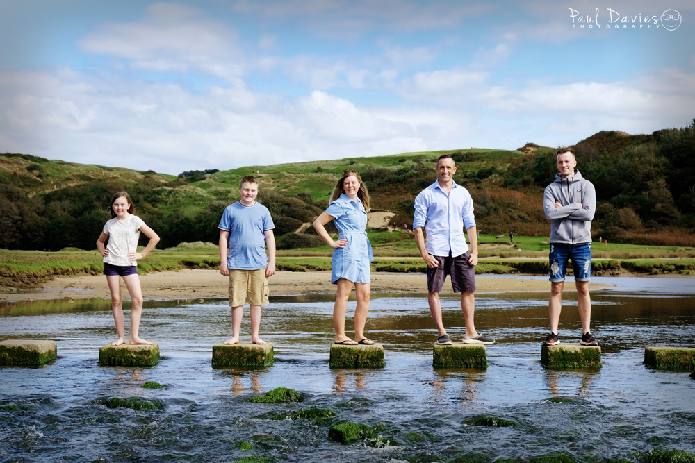 Fun family photshoot at Three Cliffs Bay Gower on stepping stones