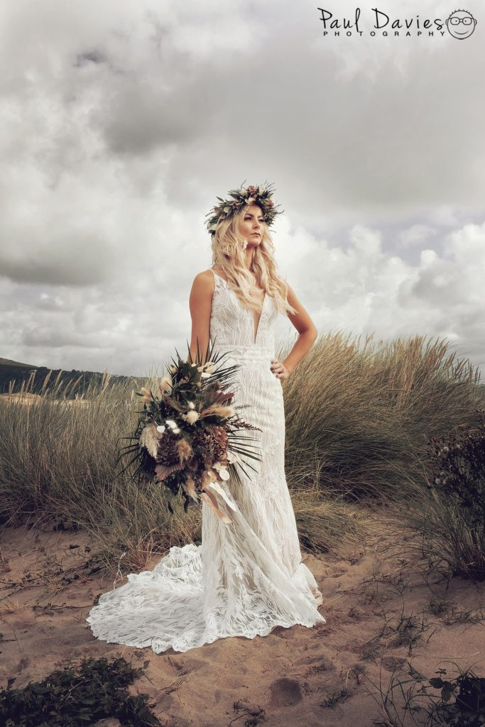 Bride with autumnal flowers in sand dunes at Oxwich bay